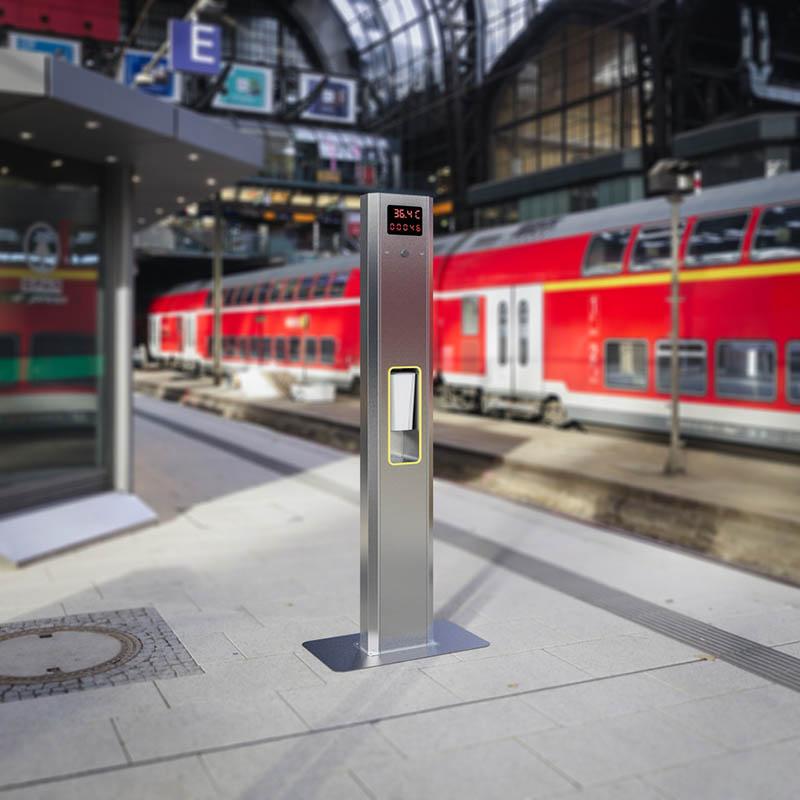 Máquina de medición de temperatura y desinfección en una estación de tren